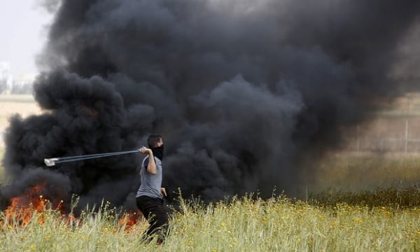 A Palestinian slings stones towards Israeli soldiers during clashes along the border with Israel. Photograph: Adel Hana/AP