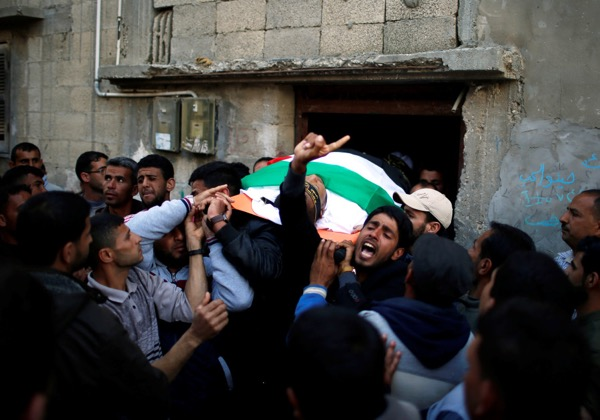 Mourners carry the body of Palestinian Faris al-Reqib, 29, who was killed during clashes at Israel-Gaza border, during his funeral in Khan Younis, in the southern Gaza Strip (photo credit: MOHAMMED SALEM/REUTERS)