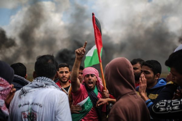 Smoke billows behind a group of Palestinians during a tent city protest along the Israel border with Gaza. Ibraheem Abu Mustafa / Reuters