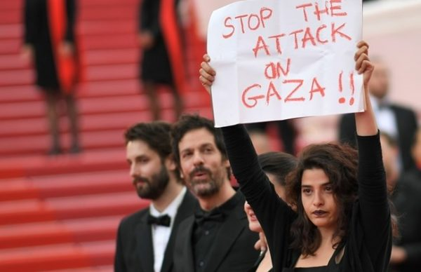 "French-Lebanese actress Manal Issa (R) holds a sign reading ""Stop the Attack on Gaza"" as she arrives on May 15, 2018 with Syrian director Gaya Jiji (2ndR) and Greek-South African film director Etienne Kallos (2ndL) for the screening of the film ""Solo : A Star Wars Story"" at the 71st edition of the Cannes Film Festival in Cannes, southern France. / AFP / LOIC VENANCE"