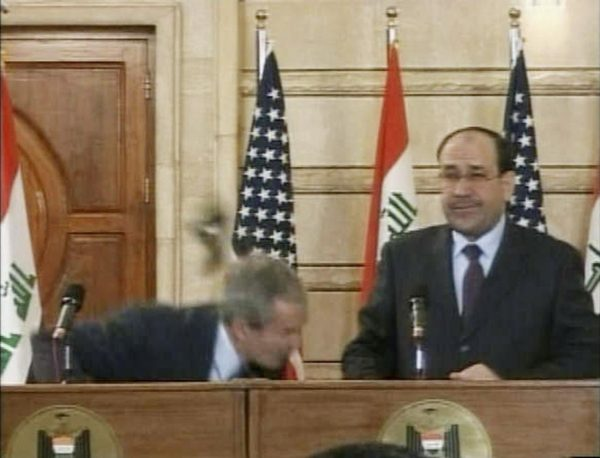 "A video frame grab shows President George W. Bush (L) ducking from a shoe thrown by Iraqi journalist Muntazer al-Zaidi during a news conference in Baghdad December 14, 2008. ""This is a farewell kiss from the Iraqi people, you dog!"" Zaidi yelled before being tackled to the ground by Iraqi Prime Minister Nouri al-Maliki's guards. REUTERS TV"