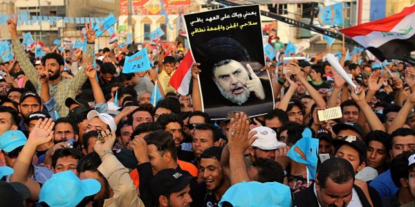 Supporters of Muqtada al-Sadr, who is seen on the poster, attend a campaign rally in Baghdad.Karim Kadim / AP file