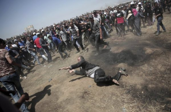 An elderly Palestinian man falls on the ground after being shot by Israeli troops during a deadly protest at the Gaza Strip's border with Israel, east of Khan Younis, Gaza Strip, Monday, May 14, 2018. Thousands of Palestinians are protesting near Gaza's border with Israel, as Israel celebrates the inauguration of a new U.S. Embassy in contested Jerusalem. (AP Photo/Adel Hana)