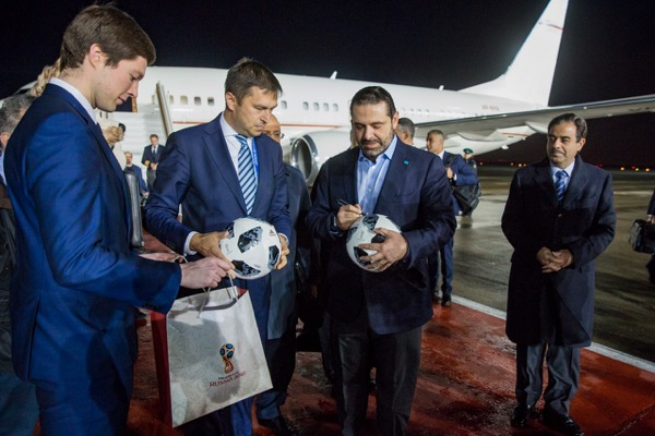 HARIRI AUTOGRAPHING A SOCCER BALL