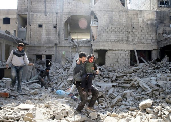A man carries an injured boy as he walks on rubble of damaged buildings in a the rebel held besieged town