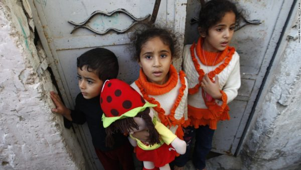 Palestinian children stand at the gate of their home as they watch a funeral procession