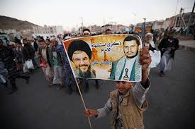 A boy holding a poster of Lebanon's Hezbollah leader and the leader of the Shi'ite Houthi movement during a rally in Sana'a, Yemen, on October 26, 2016.