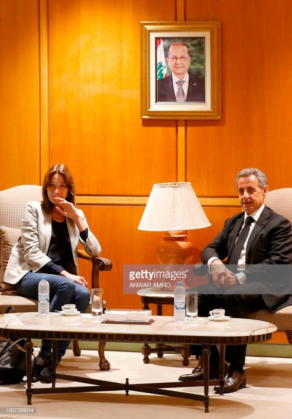 French-Italian musician Carla Bruni (L) and her husband, former French President Nicolas Sarkozy sit under a portrait of Lebanese president Michel Aoun as they arrive at the Beirut airport on July 29, 2018. - Bruni is set to perform her fifth album, French Touch, at the Beiteddine Art Festival on July 30. (Photo by ANWAR AMRO / AFP)        (Photo credit should read ANWAR AMRO/AFP/Getty Images)