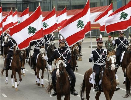 Lebanese Army troops on horseback hold Lebanese flags during a military parade to mark the 69th anniversary of Lebanon's independence from France, in downtown Beirut, Lebanon, Thursday Nov. 22, 2012. Lebanon gained independence from France in 1943. (AP Photo/Hussein Malla)