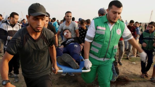 Medics and protester evacuate a wounded youth from near the fence of the Gaza Strip border with Israel during a protest east of Gaza City, Friday, Nov. 9, 2018. (AP Photo/Adel Hana)