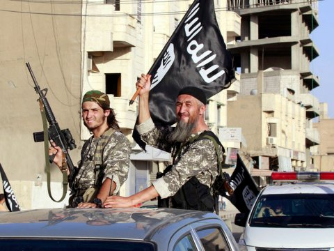 islamic-state-fighters-wave-flags-as-they-take-part-in-a-military-parade-along-the-streets-of-northern-raqqa-province-syria-june-30-2014-reutersstringer