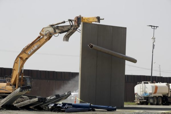The top tube of a border wall prototype falls during demolition at the border between Tijuana, Mexico, and San Diego, Wednesday, Feb. 27, 2019, in San Diego. The government is demolishing eight prototypes of Donald Trump's prized border wall that instantly became powerful symbols of his presidency when they were built nine months after he took office. (AP Photo/Gregory Bull)
