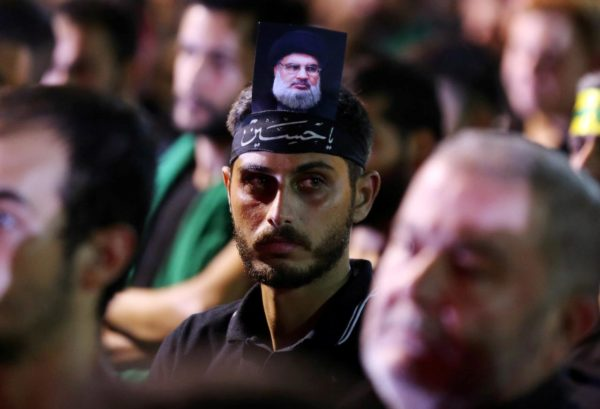 FILE PHOTO: A supporter of Lebanon's Hezbollah leader   Hassan Nasrallah has his picture on his head, during a live broadcast, the night before Muslim Shi'ites around the world mark the day of Ashura, in Beirut, Lebanon September 19, 2018. REUTERS/Hasan Shaaban/File Photo