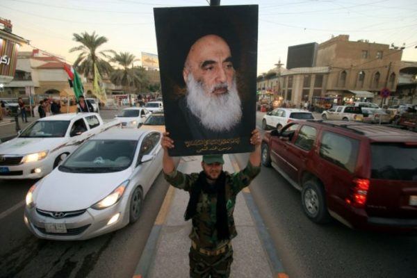 A member of the Hashd al-Shaabi (Popular Moblisation units) carries a portrait of Iraq's most revered Shiite cleric Grand Ayatollah Ali al-Sistani during victory celebrations in the southern city of Basra on December 10, 2017 HAIDAR MOHAMMED ALI (AFP