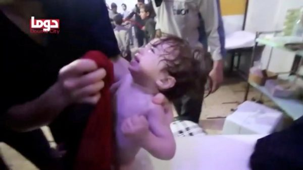 FILE PHOTO: A child cries as they have their face wiped following alleged chemical weapons attack, in what is said to be Douma, Syria in this still image from video obtained by Reuters on April 8, 2018. White Helmets/Reuters TV via REUTERS