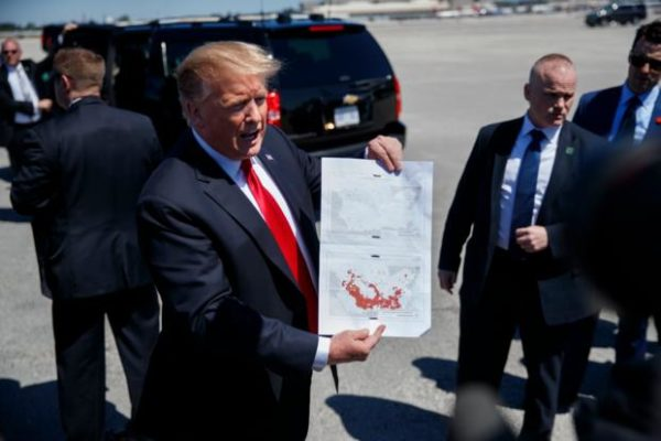 President Trump holds a a copy of two maps of Syria as he arrives on Air Force One, Friday, March 22, 2019, at Palm Beach International Airport, in West Palm Beach, Fla. (AP Photo/Carolyn Kaster)