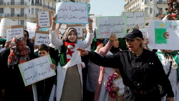 Zohra Bensemra, Reuters | A police officer directs traffic while demonstrators carry signs as teachers and students take part in a protest demanding immediate political change in Algiers, Algeria March 13, 2019.