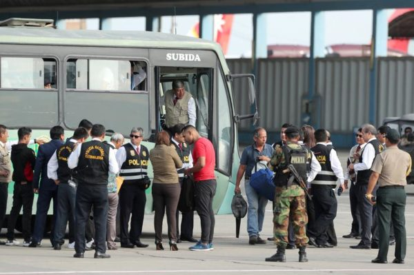 Peruvian immigration police escort Venezuelan migrants as they board a bus prior to their deportation, after being accused of concealing that they had criminal records, according to Peru's Interior Ministry, in Lima, Peru April 29, 2019. REUTERS/Guadalupe Pardo