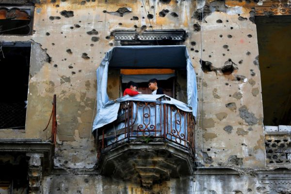 Children stand on the balcony of their apartment building that was damaged during Lebanon's 1975-1990 civil war. All photos by AP Photo