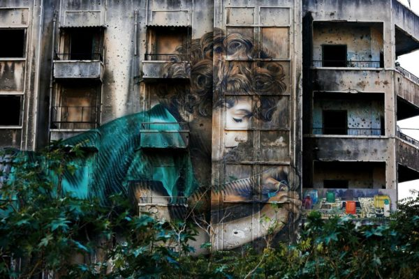 Graffiti by Cuban-American artist Jorge Rodriguez-Gerada depicting a boy is painted on a bullet riddled building.