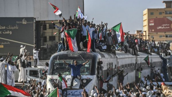 Ozan Kose, AFP | A train loaded with protesters from the town of Atbara, where Sudan's months-long unrest began, arrives in Khartoum on April 23.