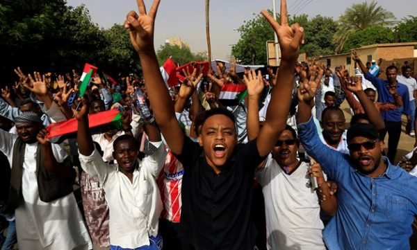A Sudanese demonstrator flashes a two finger salute as they attend a protest rally demanding Sudanese President Omar Al-Bashir to step down outside the Defence Ministry in Khartoum, Sudan April 11, 2019. REUTERS/Stringer