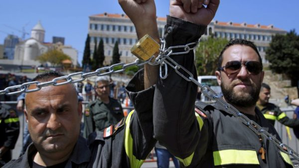 FILE - Civil Defense volunteers with symbolic metal chains around their wrists protest in front of the government building during a sit-in to demand full time jobs in fixed posts in Beirut, Lebanon, April 4, 2019.