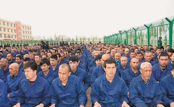 """Uighur detainees listening to a """"deradicalization"""" presentation at a camp, in a photo posted to the Xinjiang Judicial Administration's WeChat account, Hotan Prefecture, Xinjiang, 2017"""