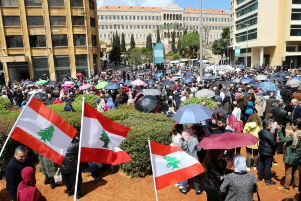 Public sector workers hold Lebanese flags during a protest against cuts to their salaries in downtown Beirut, April 17. (Reuters)