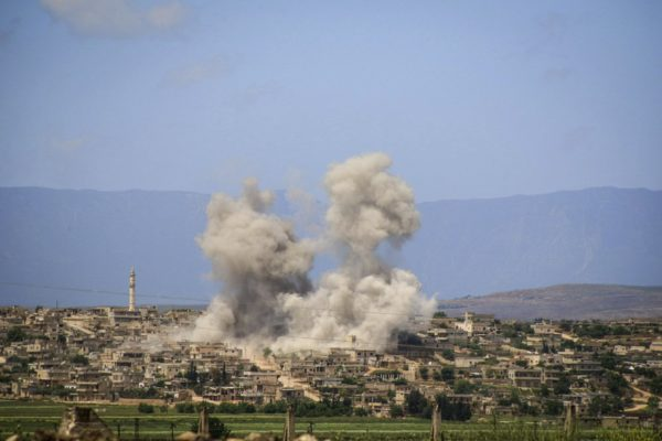 This photo provided by the Syrian Civil Defense White Helmets, which has been authenticated based on its contents and other AP reporting, shows smoke rises after Syrian government and Russian airstrikes hit the town of al-Habeet, southern Idlib, Syria, Friday, May 3, 2019. Syrian state media and activists are reporting a wave of government and Russian airstrikes, including indiscriminate barrel bombs, on the rebel-held enclave in northwestern Syria where a seven-month truce is teetering under a violent escalation. (Syrian Civil Defense White Helmets via AP)