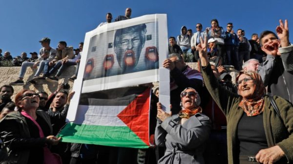 Palestinian protesters hold a poster bearing an image of Trump and the Palestinian flag during a demonstration at Damascus Gate in the Jerusalem's Old City on December 8, 2017. To the Palestinians Trump is the enemy