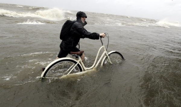 yler Holland guides his bike through the water as winds from Tropical Storm Barry push water from Lake Pontchartrain over the seawall Saturday, July 13, 2019, in Mandeville, La. (AP Photo/David J. Phillip)