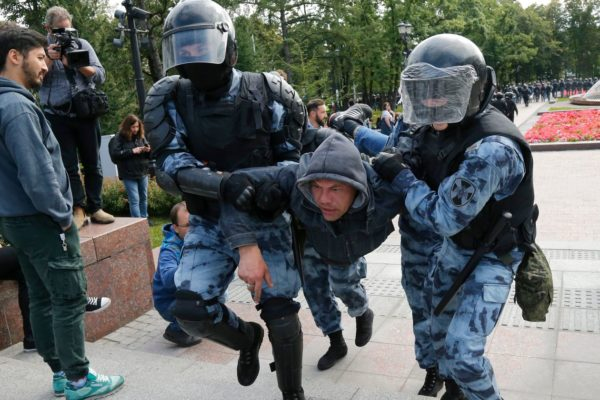 Police officers detain a protester during an unsanctioned rally in the center of Moscow on Saturday. PHOTO: ALEXANDER ZEMLIANICHENKO/ASSOCIATED PRESS