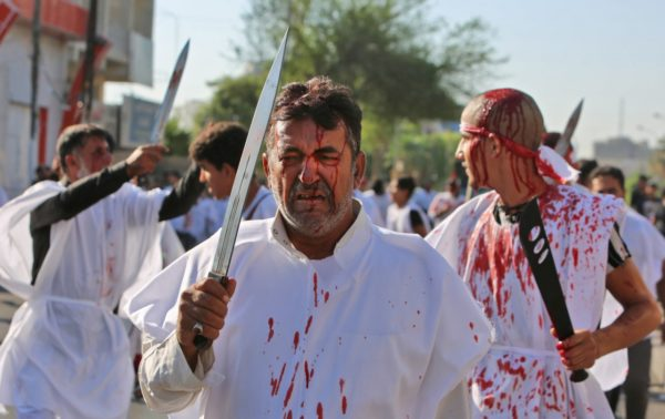 Iraqi men flagellate themselves with swords during the mourning procession on the tenth day of Muharram which marks the day of Ashura, in the Iraqi capital Baghdad on September 10, 2019. (SABAH ARAR/AFP/Getty Images)