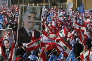 Lebanese people carry national flags and pictures of Lebanese Prime Minister Saad Hariri, left, and his father slain former Prime Minister Rafik Hariri, right, during the  rally