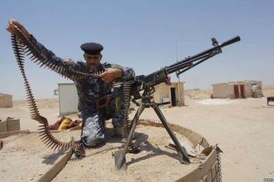 A member of the Iraqi security forces works with an ammunition belt near a weapon in the desert region between Kerbala and Najaf, south of Baghdad, June 28, 2014