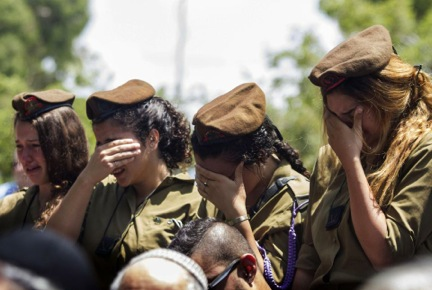 A wounded Israeli soldier arrives for the funeral of Maj. Tzafrir Bar-Or, 32, one of 13 soldiers killed in several separate incidents in Shijaiyah on Sunday, at the military cemetery in Holon, Israel, Monday, July 21, 2014.