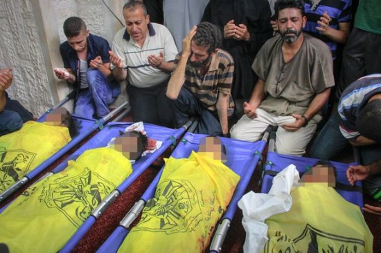 Huge Loss: Relatives of the four Baker family children, killed in Israeli Air-strikes while they were playing, seen mourning at their funeral yesterday.