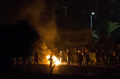 Arab youths clashed with Israeli police in the northern Israeli town of Kfar Kana, burning tires and hurling firecrackers at the security forces. It was the third straight day of unrest in the town following the shooting death of a local man by an Israeli police officer. Video of the incident indicate the man was walking away from the officer when he was shot. (AP Photo/Ariel Schalit) November 10, 2014