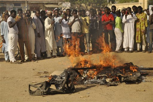 People gather at the site of a bomb explosion in Kano, Nigeria, Friday Nov. 28, 2014. An explosion tore through the central mosque in Nigeria's second-largest city on Friday, and officials feared the casualty toll would be high. Capt. Ikechukwu Eze said the Friday blast occurred at the main mosque in the city of Kano. Hundreds had gathered to listen to a sermon in a region terrorized by attacks from the militant group Boko Haram. MUHAMMED GIGINYU — AP Photo