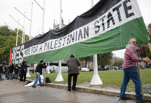 Pro-Palestinian supporters position a giant banner calling for a recognised Palestinian State, in Parliament Square, central London on Oct. 13, 2014.