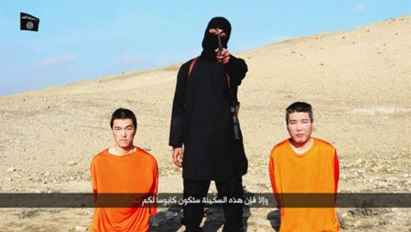 """A masked person holding a knife speaks as he stands in between two kneeling men in this still image taken from an online video released by the militant Islamic State group on January 20, 2015. The masked person was identified last week as Mohammed Emwazi, a British national  who was born in Kuwait . Until he was unmasked the world knew him better as """"Jihadi John. REUTERS/Social media website via Reuters TV"""