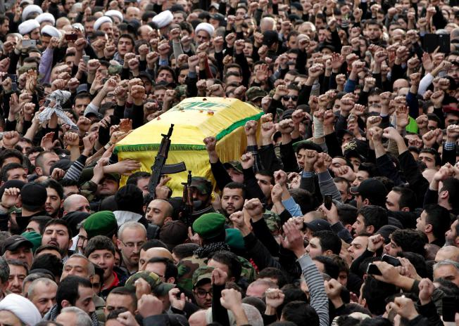 Hezbollah fighters carry the coffin of Jihad Mughniyeh, the son of Imad Mughniyeh, a top Hezbollah operative assassinated in 2008 in Damascus and one of the six Hezbollah fighters killed in what the group said was an Israeli airstrike Sunday in the Golan, during his funeral procession, in southern Beirut, Lebanon, Monday, Jan. 19, 2015.