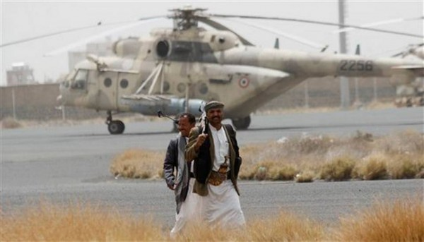"""Shiite rebels, known as Houthis, walk on the tarmac of the Sanaa International Airport in Sanaa, Yemen, Saturday, March 28, 2015. Yemen's President Abed Raboo Mansour Hadi, speaking at the opening session of an Arab summit in Egypt on Saturday, called Shiite rebels who forced him to flee the country """"stooges of Iran,"""" directly blaming the Islamic Republic for the chaos there and demanding airstrikes against rebel positions continue until they surrender. HANI MOHAMMED AP PHOTO"""