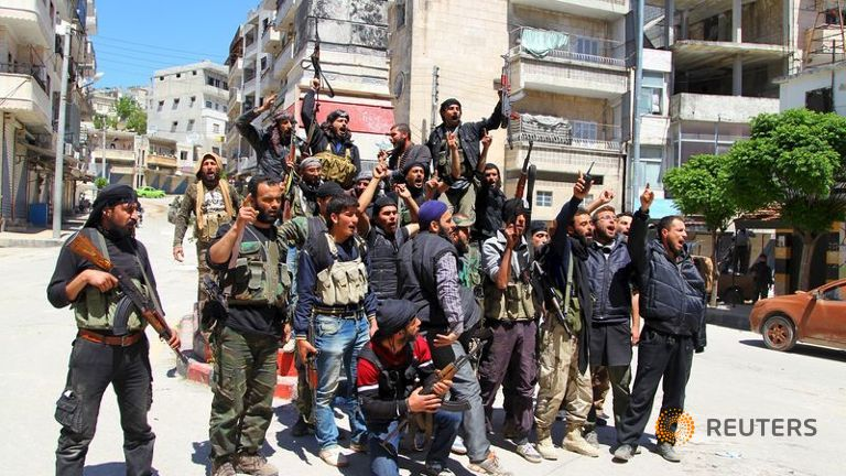 Rebel fighters celebrate with their weapons as they pose in Jisr al-Shughour town, after they took control of the area April 25, 2015.