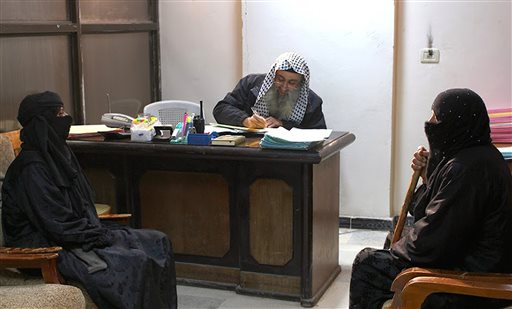 In this photo released on Feb. 10, 2015 by a militant website, which has been verified and is consistent with other AP reporting, two women sit in the office of an Islamic State group judge, center, at an Islamic court in al-Tabqa town in Raqqa City, Syria.  JUNE 18, 2015, AT 12:01 A.M. EDT. (Militant website via AP)
