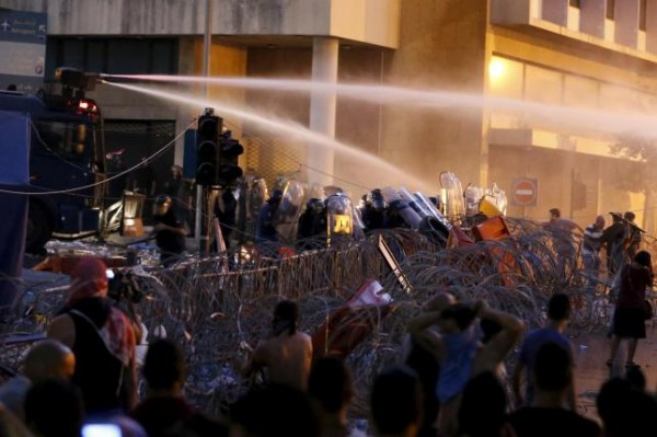 Lebanese protesters are sprayed with water during a protest against corruption and against the government's failure to resolve a crisis over rubbish disposal, near the government palace in Beirut, Lebanon August 23, 2015. REUTERS/Mohamed Azakir