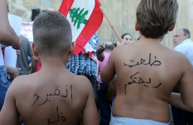 "2 kids participating in  the You Stink anti-corruption rally in Martyrs' Square in Downtown Beirut, Saturday, August 29, 2015. The Arabic words on their backs translate into  ""You Stink ""  (R) ,  and "" go to hell"""