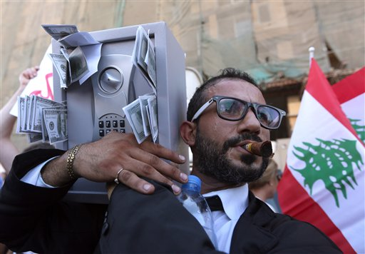 A Lebanese anti-government protester acts the role of a Lebanese politician holding a safe with fake money sticking out, during a demonstration against the trash crisis and government corruption, in downtown Beirut, Lebanon, Saturday, Aug. 29, 2015. (AP Photo/Bilal Hussein)