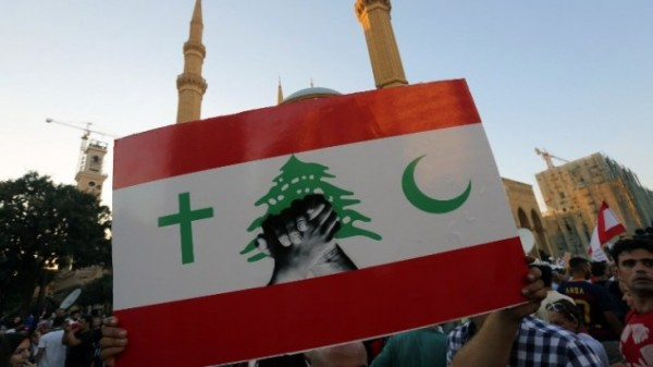 A Lebanese protester raises the Lebanese flag with the Cross and the crescent    during a mass rally against a political class seen as corrupt and incapable of providing basic services on August 29, 2015 at the iconic Martyrs Square in Beirut. (AFP PHOTO / STR)